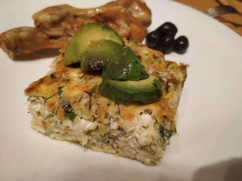 Greek style courgettes casserole with a few slices of avocado, olives and baked chicken drumsticks