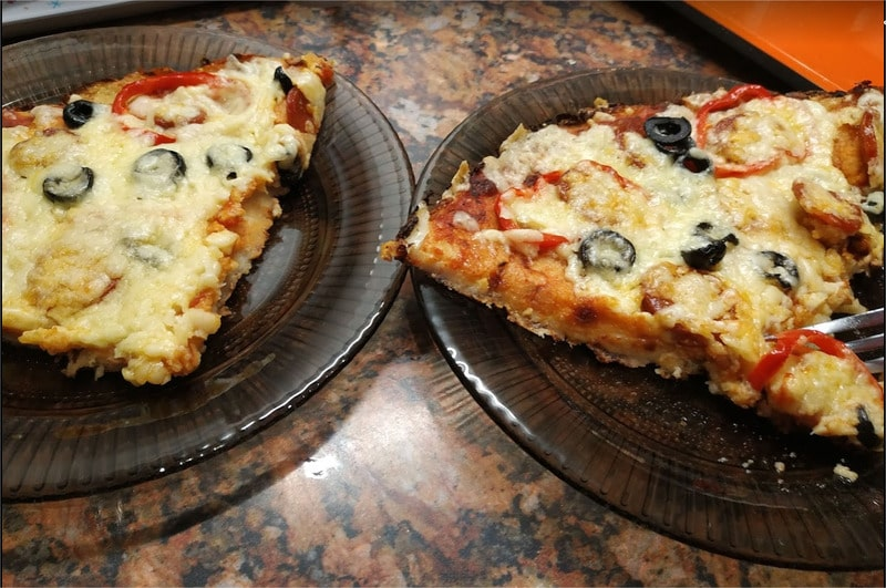 Cut the pizza into quarters Cauliflower Base Pizza