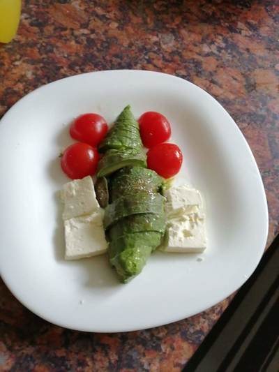 Small avocado sliced in two with a sprinkle of olive oil 2 cubes Greek feta cheese and 2 small Cherry tomatoes